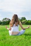 La femme médite sur la pelouse verte sur le stationnement photo libre de droits