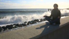 La femme médite sur la plage pendant une tempête Égalité, résistance à l'effort clips vidéos