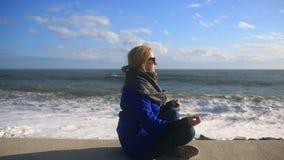 La femme médite sur la plage pendant une tempête Égalité, résistance à l'effort banque de vidéos