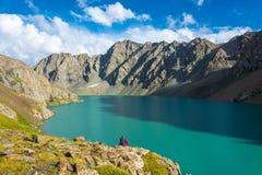 La femme médite sur le rivage d'une aile du nez-Kul de lac de montagne, Kyr Images stock