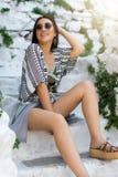 La femme méditerranéenne dans l'équipement de Bohème s'assied sur les escaliers blancs photographie stock