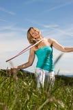 La femme mûre blonde s'exerce avec le cercle rose de hula Image libre de droits