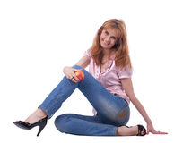 La femme mûre dans des jeans s'asseyent avec la pomme Photo stock