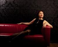 La femme mûre de beauté s'asseyent sur le sofa rouge photographie stock