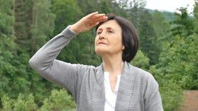 La femme mûre de brune examine la distance dans les montagnes Vacances d'été, voyages retirés banque de vidéos