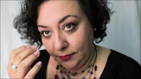 La femme mûre place le collier et regarde des cheveux banque de vidéos