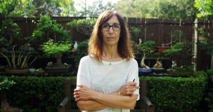 La femme mûre se tenant avec des bras a croisé dans le jardin 4k banque de vidéos