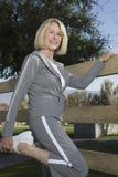 La femme mûre étire la jambe dans l'exercice d'échauffement Images stock