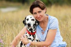 La femme mûre caresse un chien dalmatien dans un pré extérieur Image libre de droits