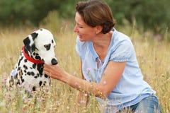 La femme mûre caresse un chien dalmatien dans un pré extérieur Photographie stock libre de droits