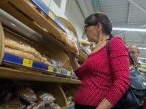 La femme mûre choisit le pain dans un supermarché Images libres de droits