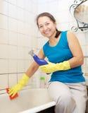 La femme mûre de sourire nettoie la baignoire Image libre de droits