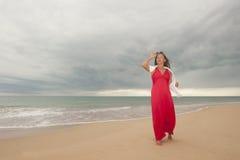 La femme mûre heureuse à la plage et avec le drak opacifie Photo libre de droits