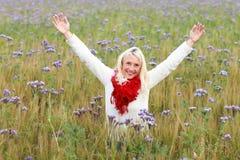 La femme mûrie heureuse avec des bras s'est étendue dans le domaine de fleur Photos stock