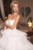La femme magnifique avec les cheveux blonds porte la robe et le bijou de mariage luxueux Photos stock