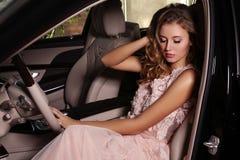 La femme magnifique avec les cheveux foncés porte la robe luxueuse, posant dans la voiture noire photo libre de droits