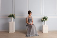 La femme magnifique dans la robe transparente s'assied sur la chaise photographie stock