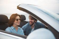 La femme magnifique et l'homme positif s'asseyent dans l'automobile Image libre de droits