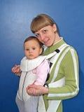 La femme maintient le bébé dans une bride de bébé Photographie stock libre de droits