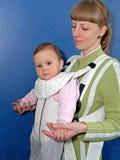La femme maintient le bébé dans une bride de bébé Images libres de droits