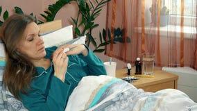 La femme malade mesurent sa température avec le thermomètre électronique se situant dans le lit banque de vidéos