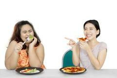 La femme mange de la pizza tout en raillant son ami Image libre de droits