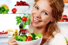 La femme mange de la salade végétarienne végétale de nourriture saine au sujet du refrige Image libre de droits