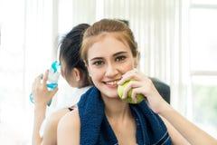 La femme mange de la nourriture saine de pomme avec de l'eau potable d'ami Image stock
