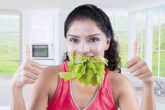 La femme mange des épinards à la maison Images stock