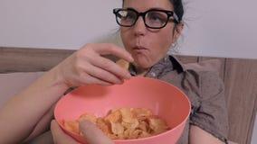 La femme mange des pommes chips banque de vidéos