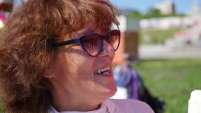 La femme mange la crème glacée en parc Nourriture en plein air Photo stock