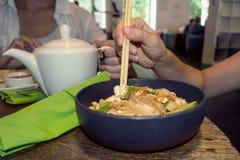 La femme mange le repas de nouilles avec le tofu image libre de droits