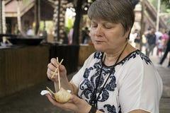 La femme mangeant du riz chinois de baguettes a fait cuire dans le bambou Photographie stock libre de droits