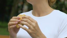 La femme mangeant l'hamburger, sent la douleur soudaine dans l'abdomen supérieur, gastrite, nourriture industrielle clips vidéos