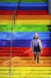 La femme marche dans les escaliers de couleur arc-en-ciel Images stock