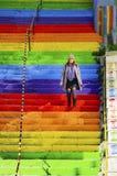 La femme marche dans les escaliers de couleur arc-en-ciel Image stock