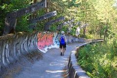 La femme marche jusqu'en 1984 des ruines olympiques de bobsleigh, Sarajevo Photo stock