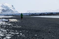 La femme marche le long de la plage noire de sable dans Vik, Islande Photographie stock