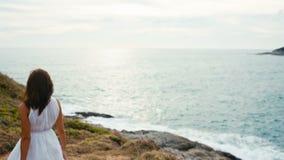 La femme marche le long du bord de la falaise et regarde l'océan sans fin le coucher du soleil clips vidéos