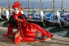 Femme masquée avec la coiffe rouge Photos stock