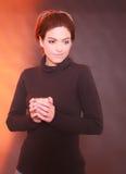 La femme merveilleuse chauffe ses mains sur une tasse Photos stock