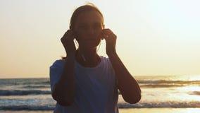 La femme met des ?couteurs pour ?couter musique avant de pulser sur la plage de mer banque de vidéos