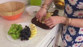 La femme met dessus un plat des tranches de banane banque de vidéos