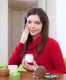 La femme met la crème sur le visage à sa maison Image libre de droits