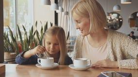 La femme met la cuillère dans la tasse du ` s de fille au café banque de vidéos