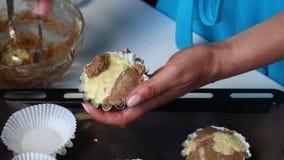 La femme met les morceaux de la pâte dans des moules de cuisson Condense la pâte dans un plat de torréfaction Préparation du gâte clips vidéos