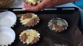 La femme met les morceaux de la pâte dans des moules de cuisson Condense la pâte dans un plat de torréfaction Préparation du gâte banque de vidéos
