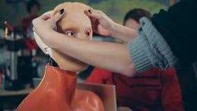 La femme met la peau sur le visage des droid, fin