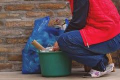 La femme mettant les déchets peut dedans et le sachet en plastique photographie stock libre de droits