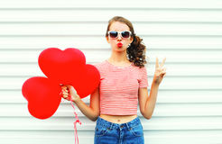 La femme mignonne de portrait faisant le baiser d'air avec le rouge monte en ballon la forme de coeur au-dessus du blanc Photos libres de droits